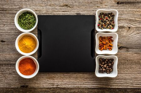 black tray with different spices in bowls on both sides