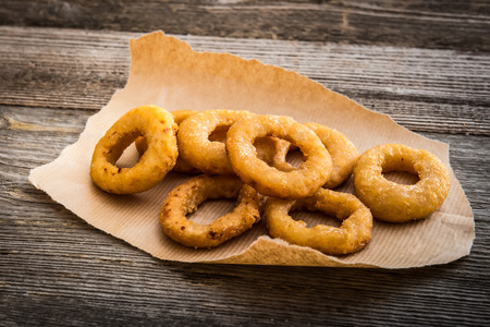 onion rings: fried onion rings on parchment on a wooden background