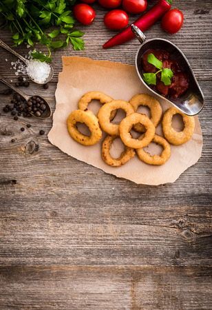 onion rings: fried onion rings on parchment with sauce and vegetables on a wooden background
