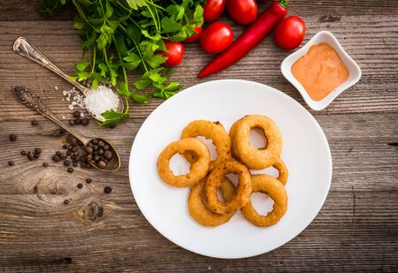 onion rings: onion rings on plate with sauce and vegetables on a wooden background Stock Photo