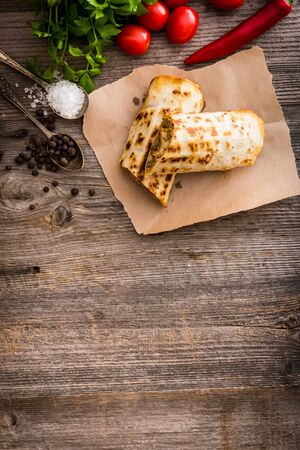 burrito: burrito on parchment with vegetables and spices on a wooden background Stock Photo