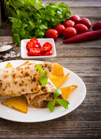 wraps: burrito with chips on plate and vegetables on a wooden background