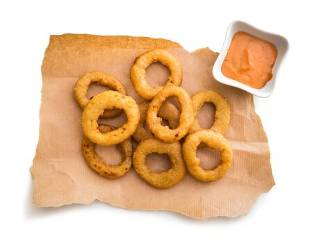 onion rings: onion rings on parchment with sauce isolated on a white background