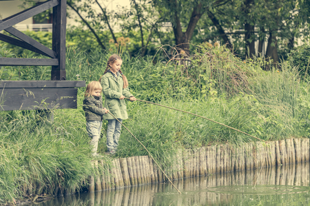 river bank: two little fisher girls with rods on a river bank