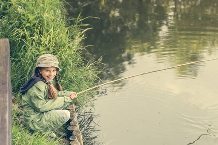 fisher: little fisher girl sitting on a river bank with a rod smiling