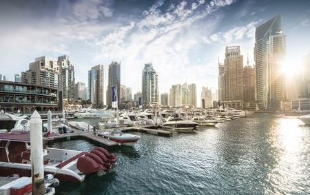 Dubai, United Arab Emirates - December 14, 2013: Panoramic view with modern skyscrapers and water pier of Dubai Marina at sunset, United Arab Emirates Editorial