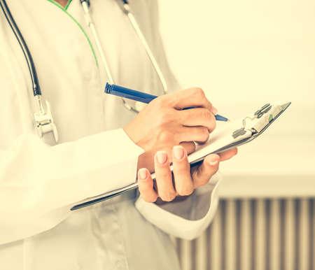 recetas medicas: médico de pie y tomando notas en un cuaderno Foto de archivo