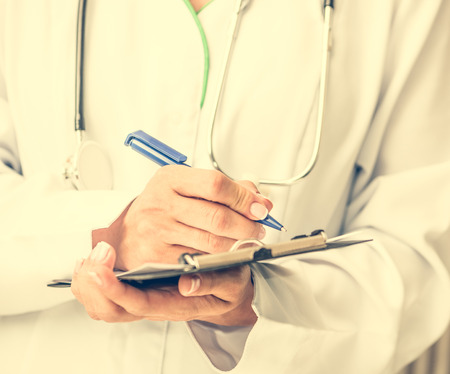 making notes: doctor standing and making notes in a notebook
