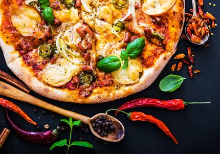jamon y queso: sabrosa pizza en un fondo negro con especias y hierbas