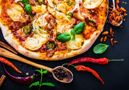 pizza crust: tasty pizza on a black background with spices and herbs