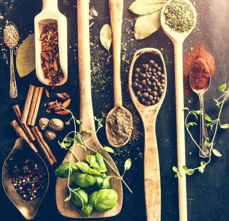 pimenton: cucharas de madera con las especias y las hierbas en el fondo negro de textura