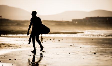 silueta hombre: Silueta del hombre caminando en la playa con la tabla de surf Foto de archivo
