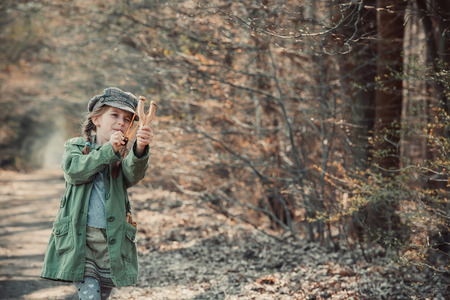 vintage photo: little girl playing with a slingshot in the woods, photo in vintage style