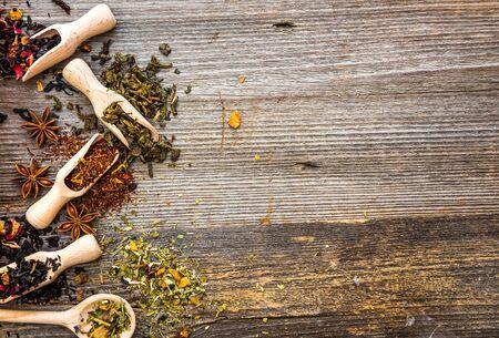hojas secas: perfumado té en cucharas y cucharones en el fondo de madera