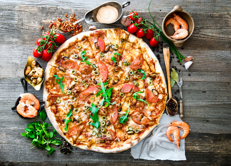 pizza dough: Big tasty pizza with seafood, tomatoes on a wooden table Stock Photo
