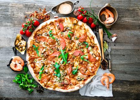 camaron: Gran sabrosa pizza con mariscos, tomates en una mesa de madera