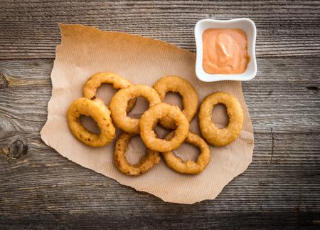 cebolla: aros de cebolla fritos en pergamino con salsa sobre un fondo de madera