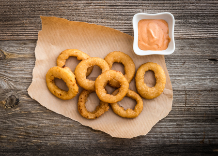 onion: fried onion rings on parchment with sauce on a wooden background