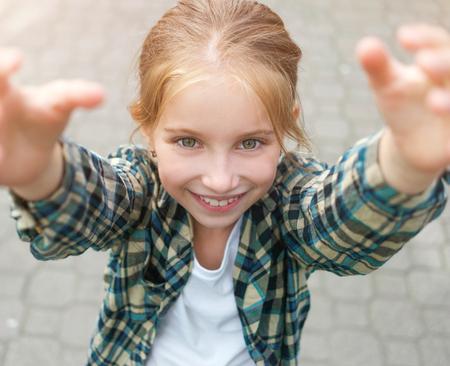 preguntando: niña bonita con los brazos arriba para llegar a algo