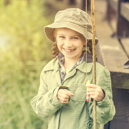 fisher: little fisher girl smiles holding a rod