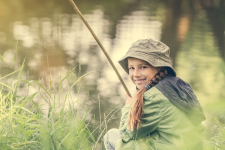 little: little fisher girl smiles sitting near a river with a rod