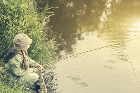 pecheur: petite fille de pêcheur assis sur une berge de la rivière avec une tige