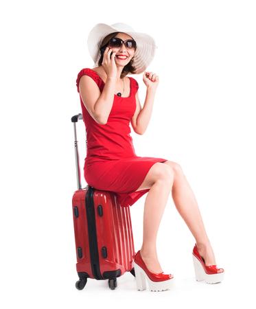 persona alegre: niña sentada en una maleta y hablando por un teléfono