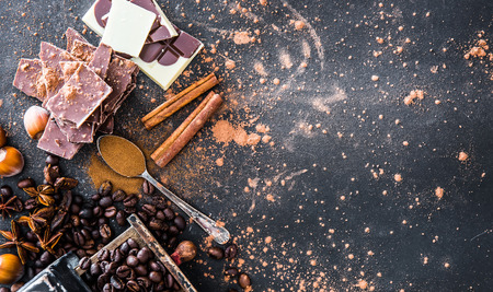Chocolate, nuts, spices on a smooth black table