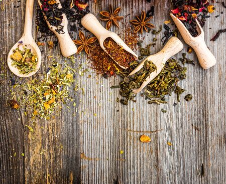 scented: scented tea in spoons and scoops on wooden background Stock Photo