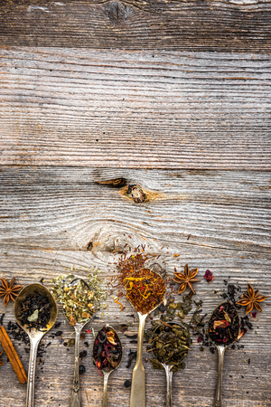 hojas secas: surtido de tés secas en cucharas de plata sobre fondo de madera