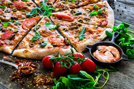 gourmet pizza: Tasty seafood pizza with cherries on a wooden table