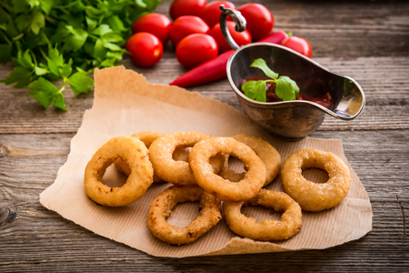 salt pepper: fried onion rings on parchment with sauce and vegetables on a wooden background