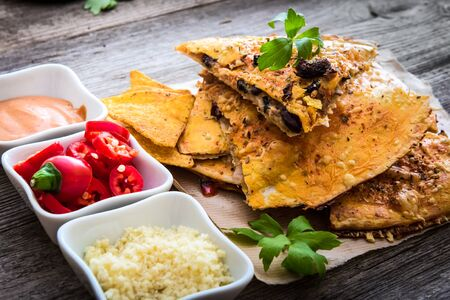 sause: quesadilla on parchment with sause and spices on a wooden background