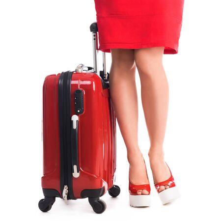 tacones rojos: maleta roja y piernas de la niña con vestido rojo y zapatos de tacón Foto de archivo