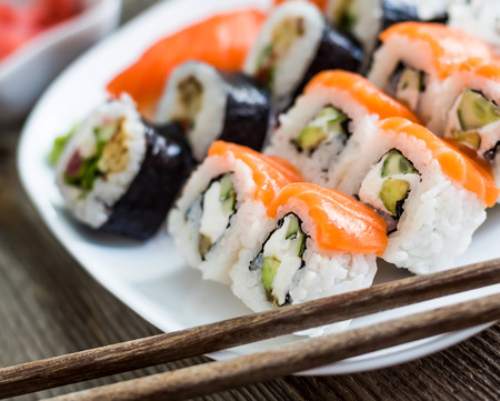 sushi roll: various sushi on white plate with chopsticks on wooden background