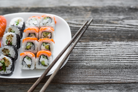 various sushi on white plate with chopsticks on wooden background
