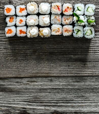 for text: assorted set of shushi and a space for text on wooden background