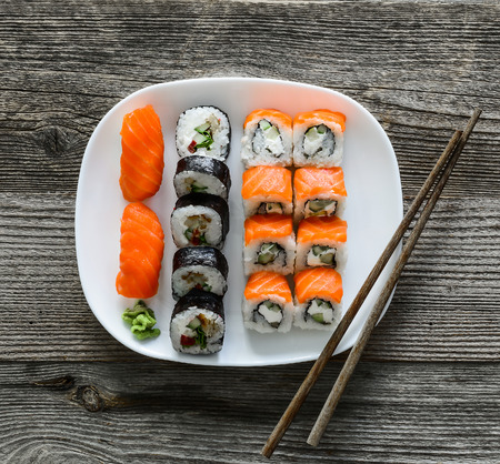 fish plate: various sushi on white plate with chopsticks on wooden background