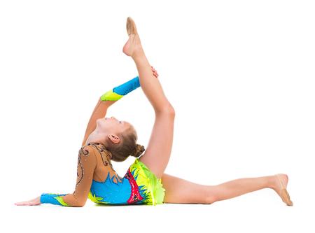 gymnastics sports: tittle gymnast doing stretching exercise isolated on white background Stock Photo