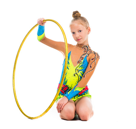 isolaten: little gymnast sitting on the floor with hoop isolaten on white background