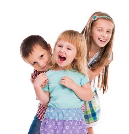 niños felices: tres niños lindos sonriente aislados sobre fondo blanco Foto de archivo