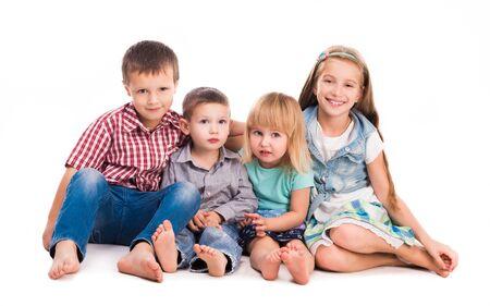 niños sentados: cuatro niños lindos que se sientan en el suelo aislado en el fondo blanco
