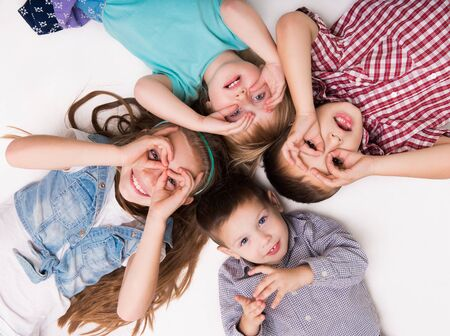 whithe: children lying on the floor with hands imitating glasses Stock Photo