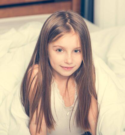mignonne petite fille: mignonne petite fille couchée dans un mauvais sous une couverture