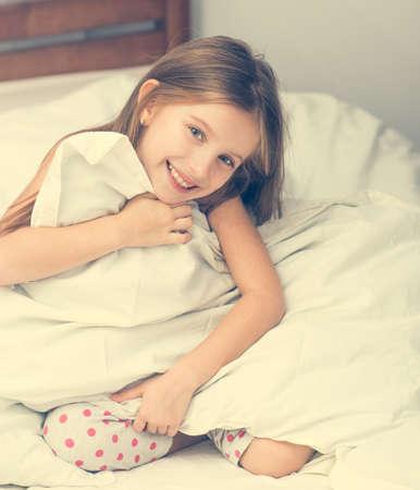 despertarse: niña linda en una mala sosteniendo una manta