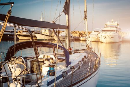 berth: yacht in a berth on blue sea and blue sky background