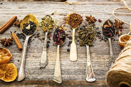 teas: assortment of dry teas in silver spoons on wooden background Stock Photo