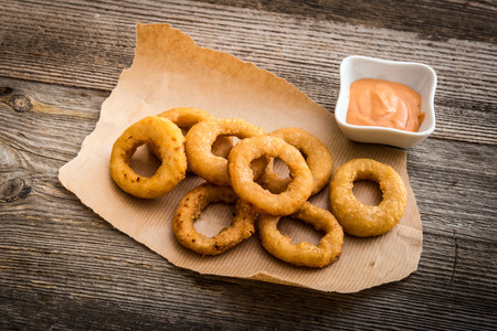 onion rings: fried onion rings on parchment with sauce on a wooden background