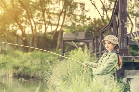 fishing bobber: little fisher girl holdin a rod at a river near a bridge