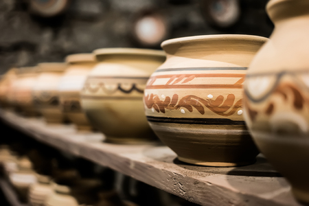 showpiece: decorated clay pots on shop shelf Stock Photo